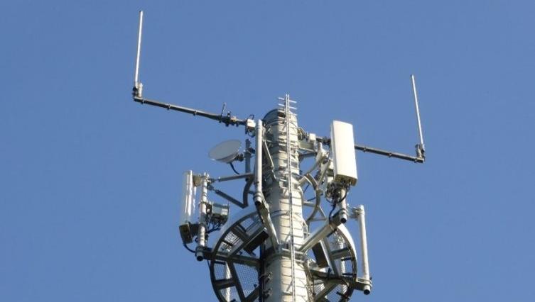 Mobilfunkmast mit LTE Antenne vor blauen Himmel