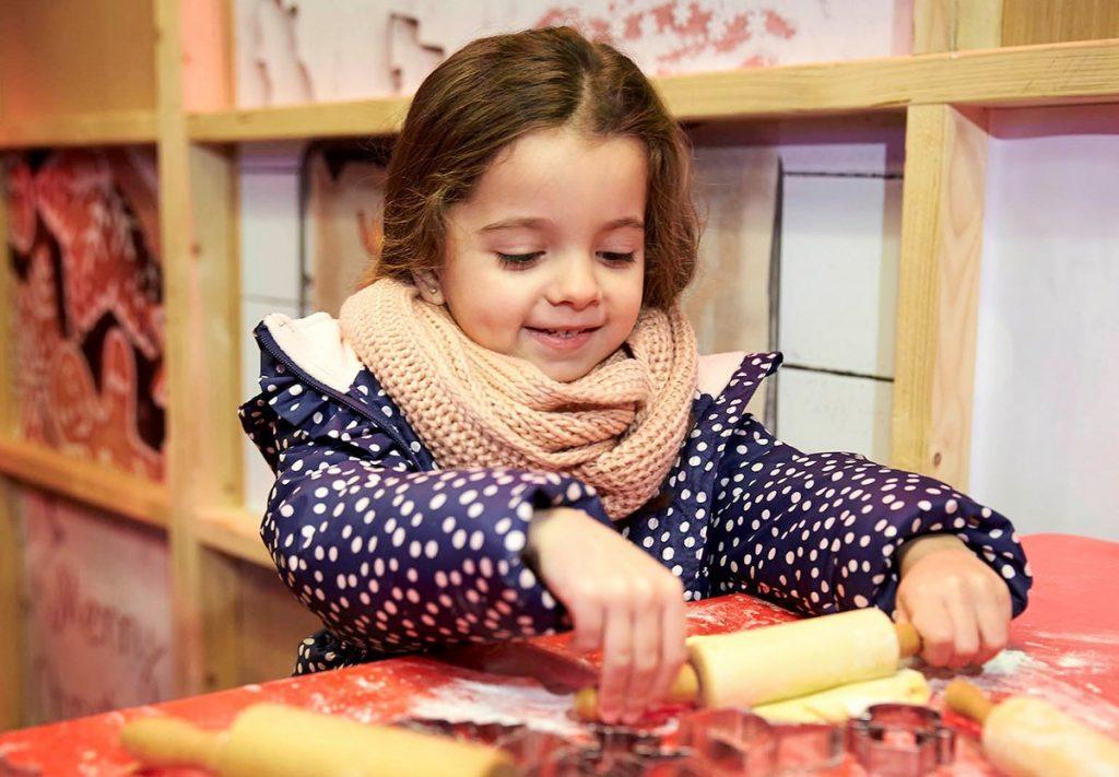 Ein kleines Mädchen backt Weihnachtsgebäck