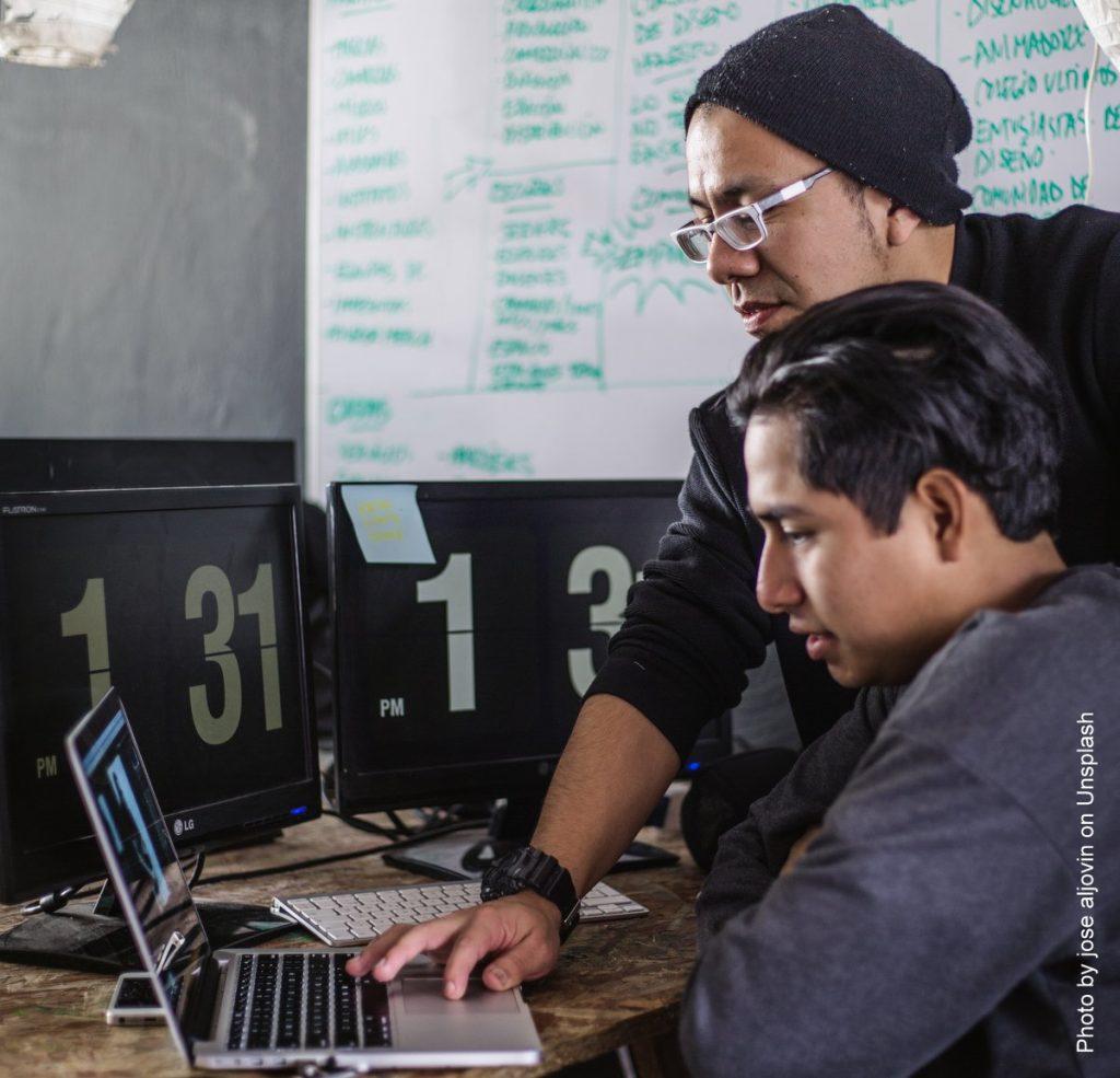 Zwei junge Männer am Laptop, der eine hilft.