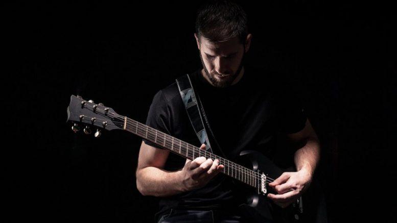 Musiker mit Gitarrre spielt im Dunkeln
