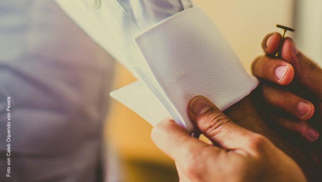 Eine Frau bindet einen Manschettenknopf