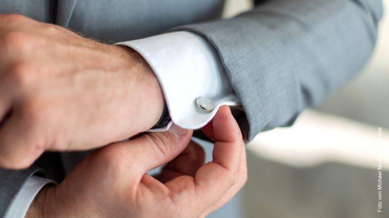 Mann im grauen Anzug mit Manschettenknopf