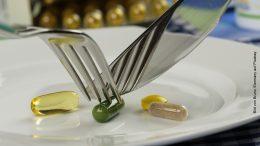 Symbolbild Medikamente auf einem Teller werden mit Messer und Gabel genomen