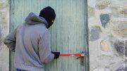Einbruch: Ein Mann bricht mit einem Stemmeisen eine Haustür auf, Symbolbild