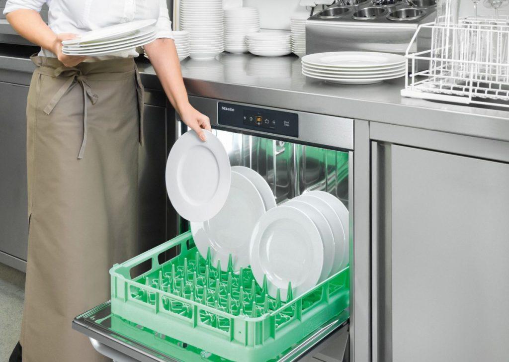 Ein Geschirrspüler in einer Restaurantküche wird mit Tellern gefüllt