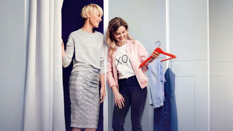Zwei Frauen an einer Umkleidekabine probieren Mode an