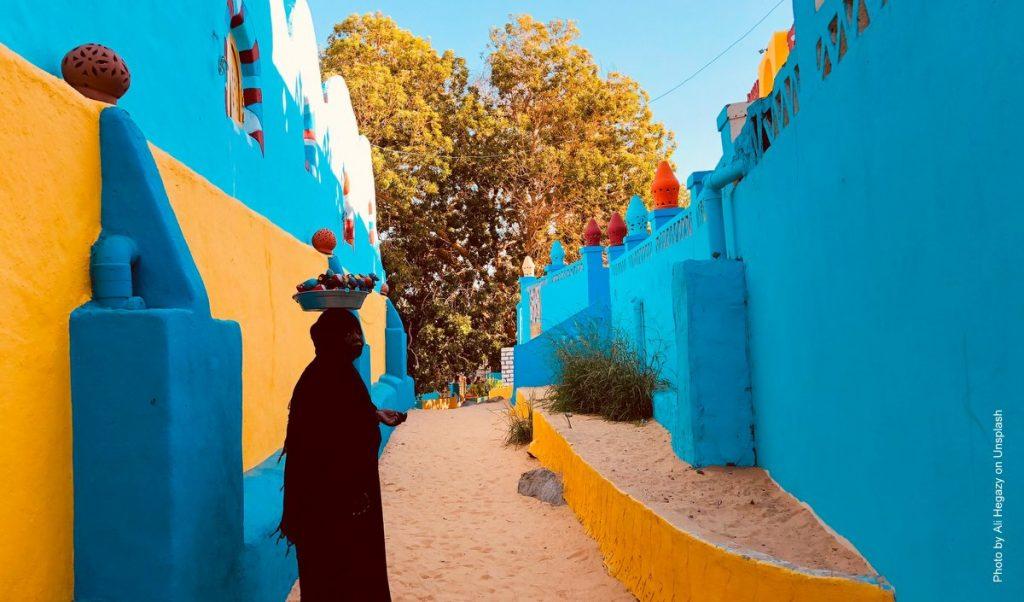 Gasse mit blauen Wänden in Ägypthen mit Frau im Vordergrund