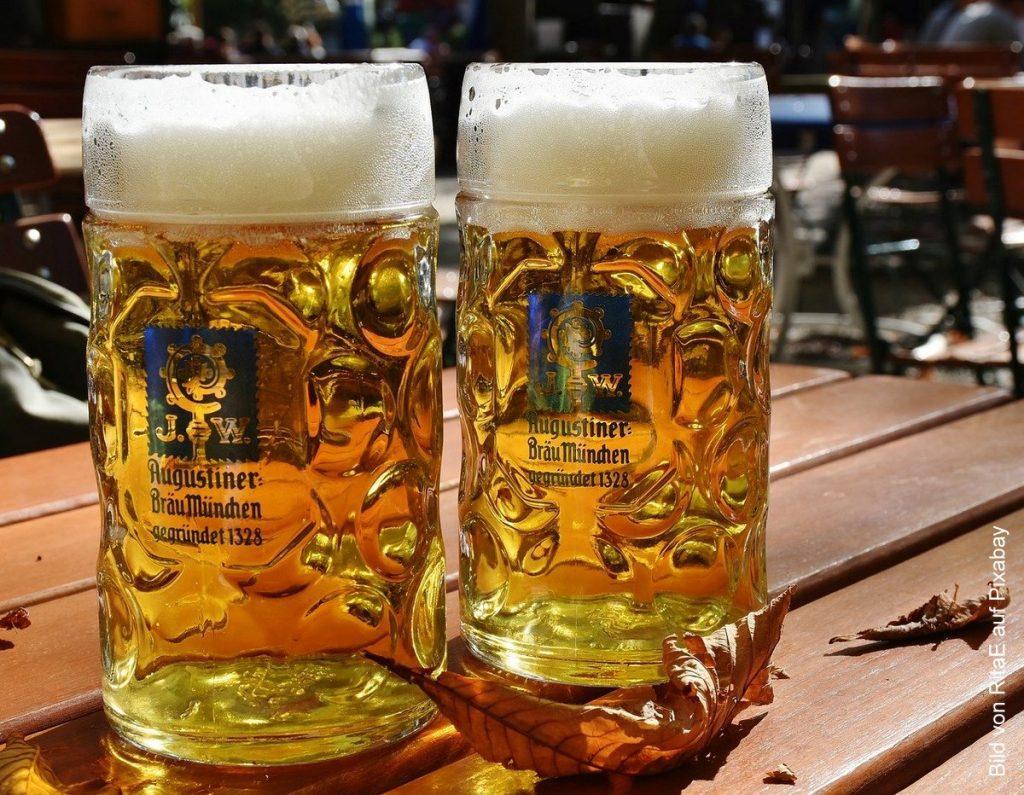 Zwei Bierkrüge aus Glas im Biergarten auf einem Tisch