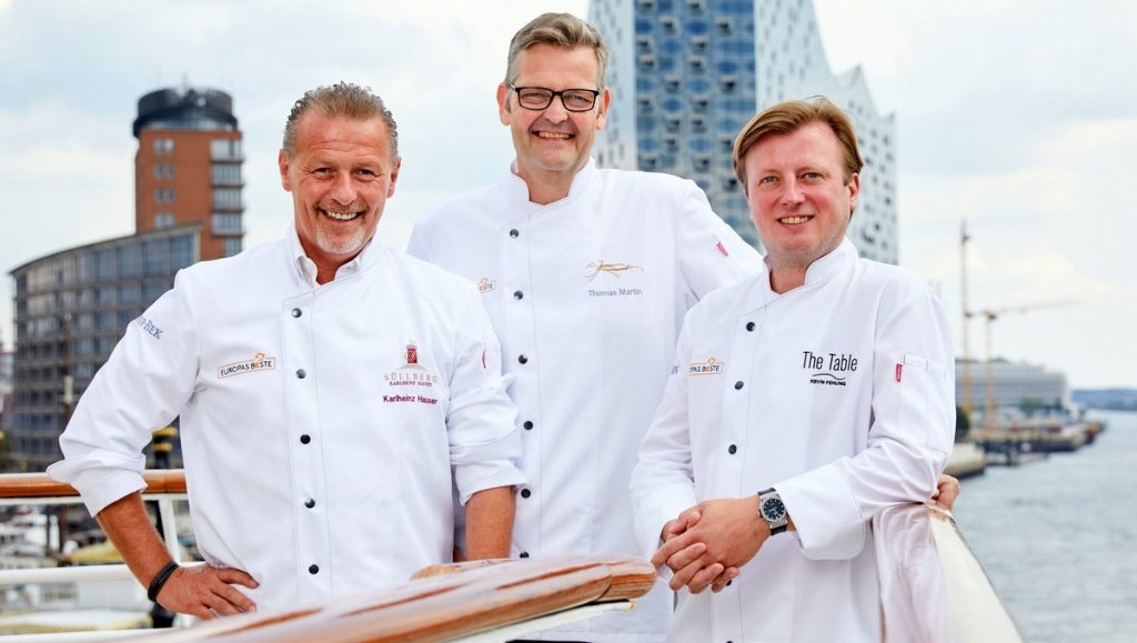 Die drei Sterne Köche Karlheinz Hauser, Thomas Martin, Kevin Fehling an Bord der MS Europa im Hintergrund die Elbphilharmonie