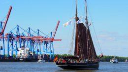 Containerschiff und Zweimast-Segler auf der Elbe