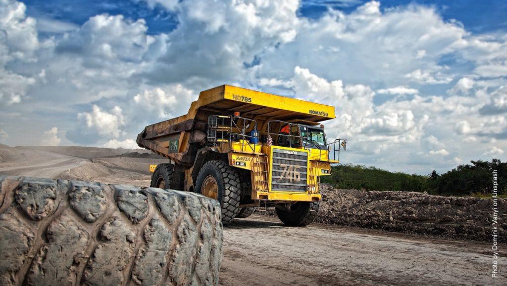 Großer gelber Truck im Tagebau vor blauem HImmel