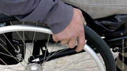 Rollstuhl - Detailaufnahme mit Hände am Laufrad
