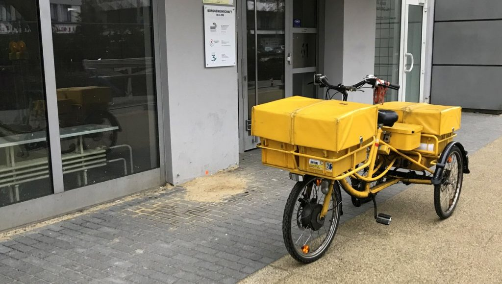 Gelbes DHL, Post, Zustellfahrrad vor einer Haustür