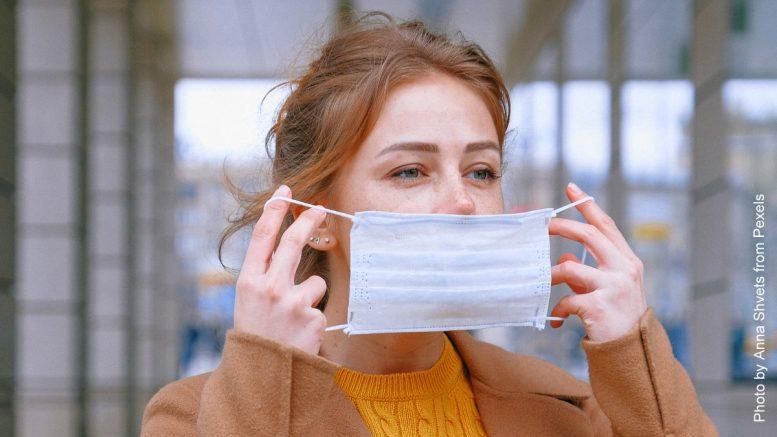Corona Lockdown: Blonde Frau legt eine Gesichtsmaske an