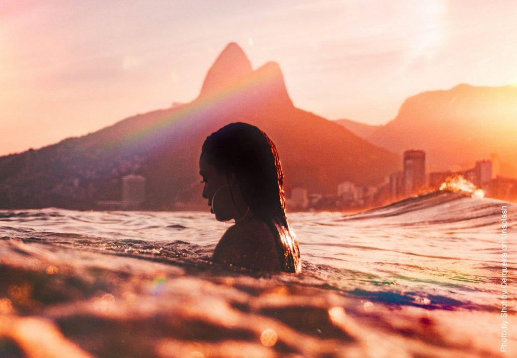 Eine junge Frau badet abends im Ipanema Strand in Rio de Janero