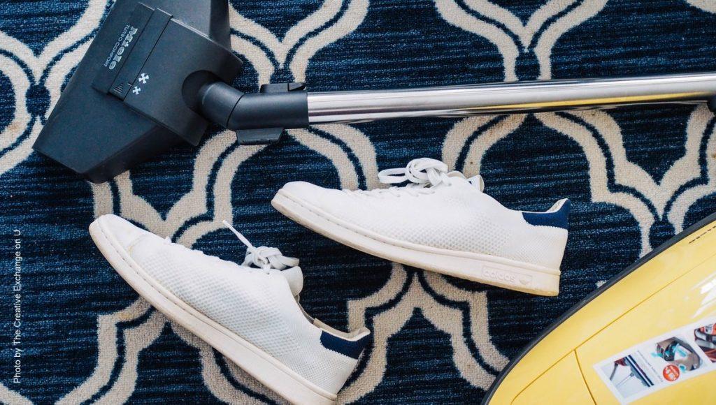 Staubsauger von Miele mit 2 weißen Sneakers