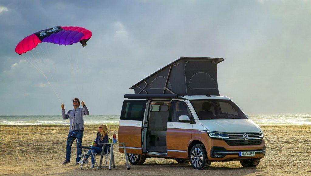 VW California am Strand mit Paar und Flugdrachen