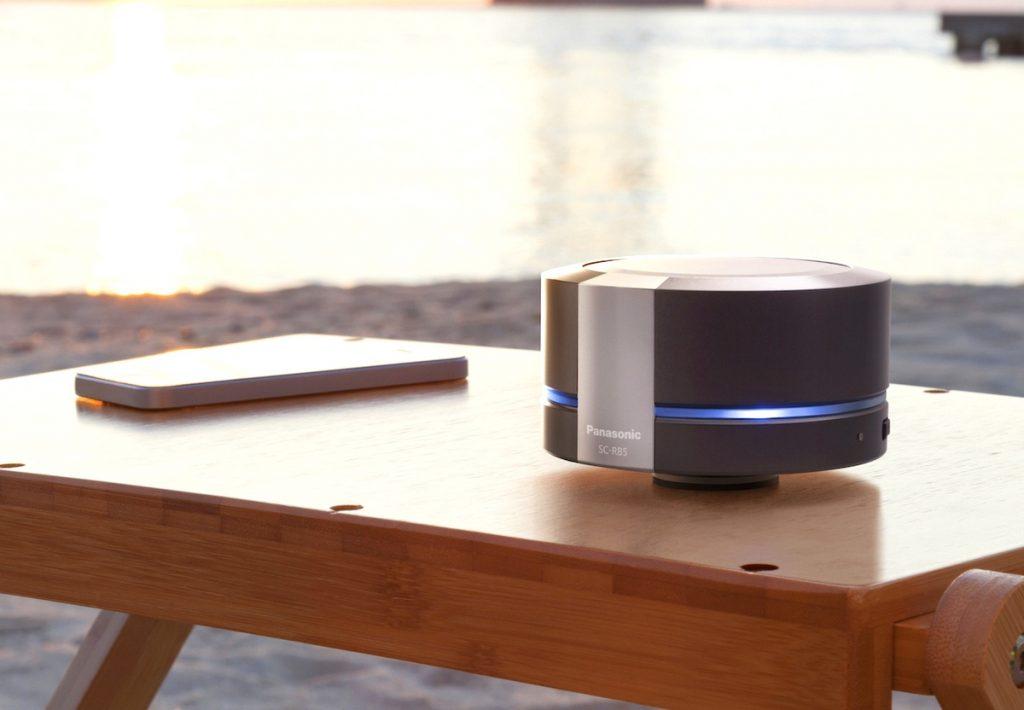 Bluetooth Lautsprecher von Panasonic am Strand auf einem Teaktisch