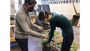Ein Mann und eine Frau, beide mit Corona-Schutzmaske, packen Lebensmitteltüten in Hamburg