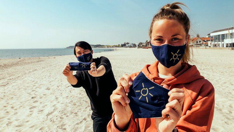 junge Frau und junger Mann am Strand von Grömitz mit den Grömitz-Corona-Masken für die Corona-Lockerungen