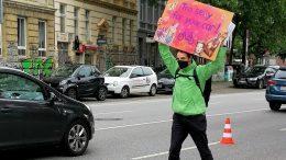 Demonstation für Pop up Radweg in Hamburg. Demonstrant hält Plakat hoch.