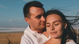 Paar trifft sich an der Nordsee. Frau wird vom Mann gehalten