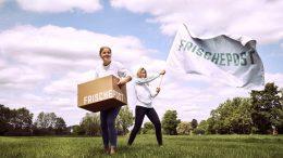 Eva Neubauer mit Lieferbox und Juliane Willing mit Flagge Frischepost auf einer Wiese. PR-Aufnahme