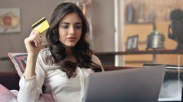 Junge Frau mit dunklen Haaren und einem silbernen Laptop hält eine Kreditkarte hoch