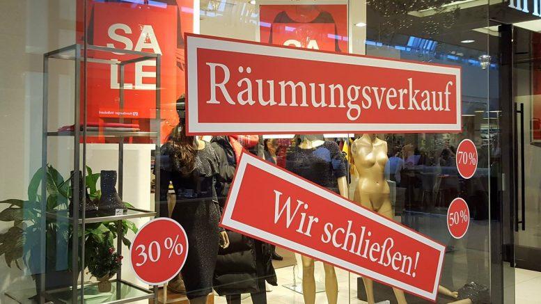 Schilder an einem Schaufenster die auf Sale und Räumungsverkauf hinweisen