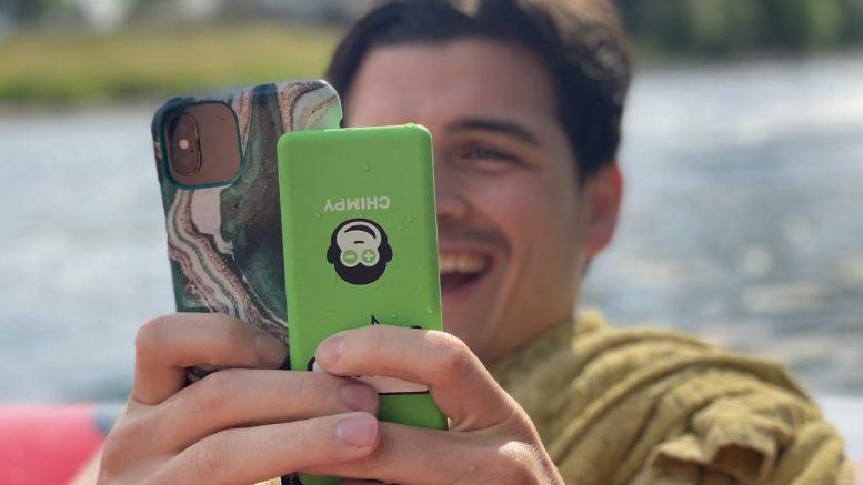 Mann mit Smartphone und Powerbank von Chimpy outdoor am Wasser