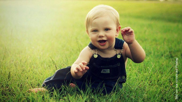Kleines Kind in Jeanslatzhose im Gras