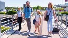 Familie, Mutter, Vater, 2 Kinder im Koffern gehen zum Hamburger Flughafen