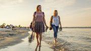 Zwei Frauen waten durchs Wasser am Ostseestrand