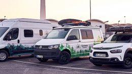 drei Camper und Wohnmobile auf einem Parkplatz