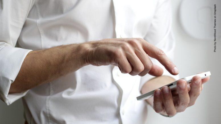 Mann mit weißem Hemd tipp in ein Smartphone