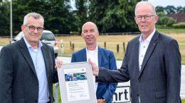 Autohaus Elmshorn erhält Serviceauszeichenung von Volkswagen. Drei Männer mit Urkunde.