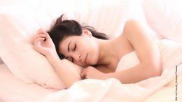 Dunkelhaarige Frau schläft im Bett