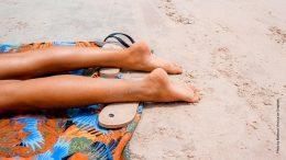 Beine einer Frau beim Sonnenbaden am Strand