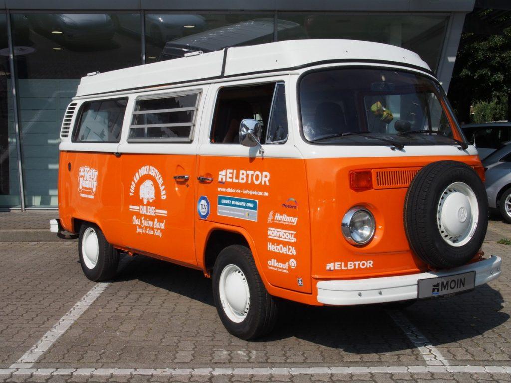 Ein Bulli T2 Camper in weiß und orange, Baujahr 1972
