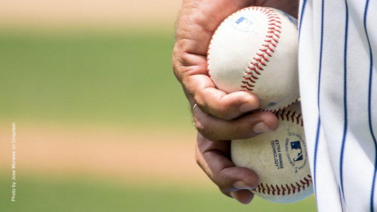 Baseballspieler hält zwei Bälle