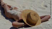 Nackte Frau mit Sonnenhut am Strand