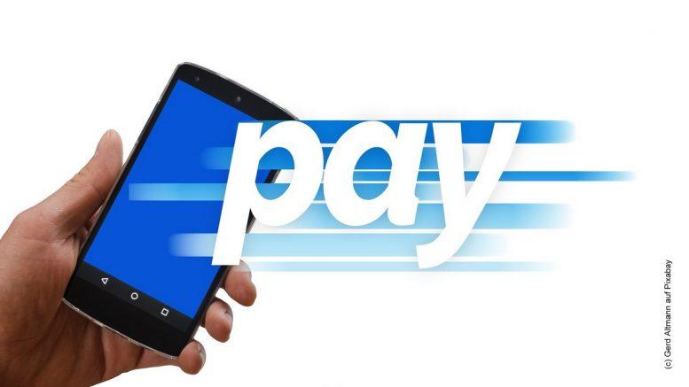 Online bezahlen - Symbolbild - Hand, Mobiltelefon mit Schriftzug pay