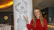 Tessa Aust im neuen Reep Restaurant zeigt auf ein Raum-Tattoo