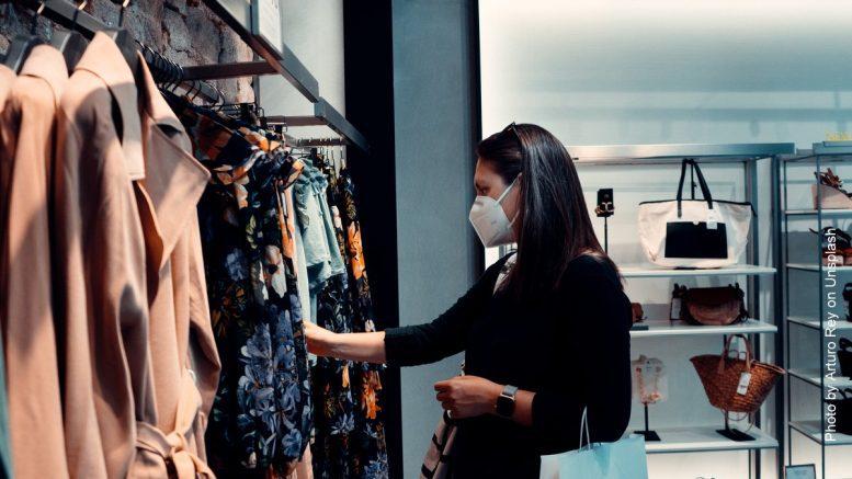 Frau mit Coronamaske beim Kleidungs-Shopping