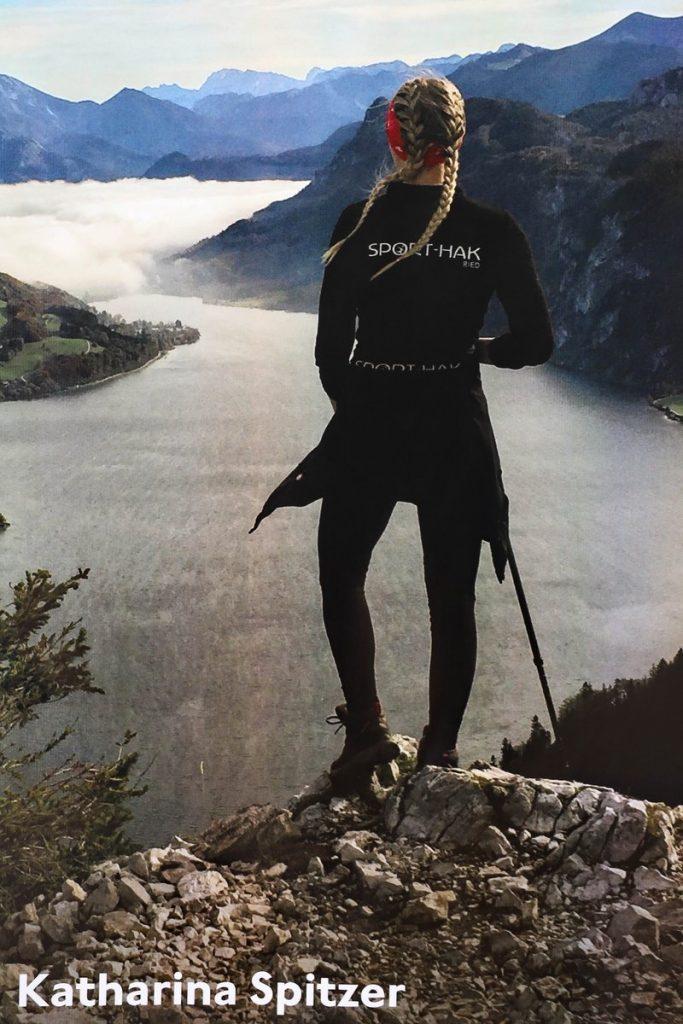 Frau schaut mit dem Rücken zur Kamera übre eine Fjord