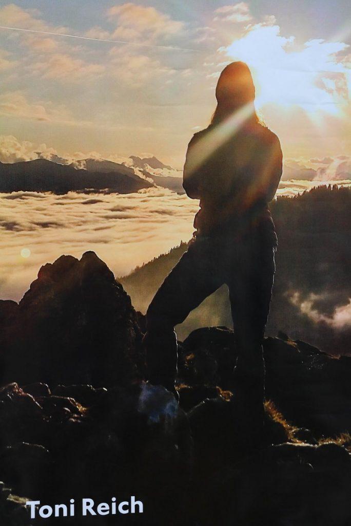 Mann schaut mit dem Rücken zur Kamera auf ein Tal mit dichten Wolken