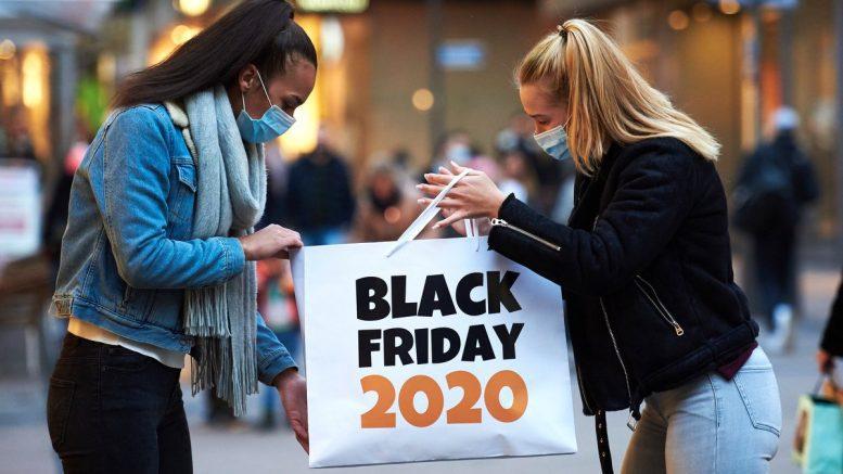 Zwei junge Frauen mit Black Friday Tüte und Mundschutz