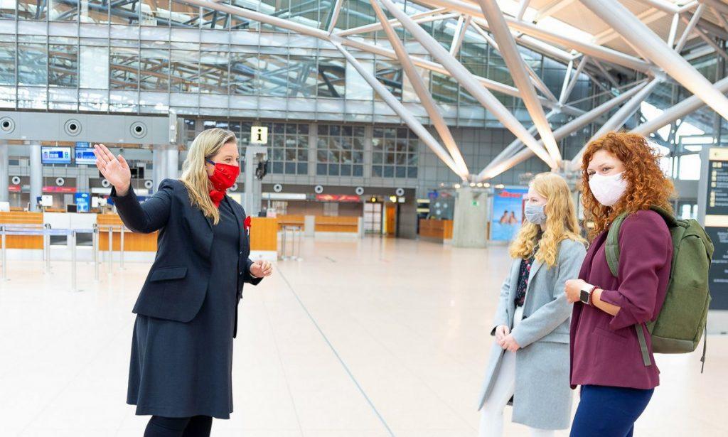 Corona-Pandemie, alle tragen am Hamburg Airport Mundschutz. Zwei Reisende fragen eine Airport-Mitarbeiterin