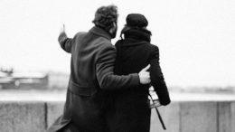 Paar geht am Wasser spazieren schwarzweiß Foto