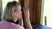 Frau schaut durchs Fernglas
